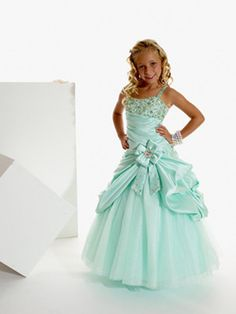 This sophisticated Tiffany Princess 13263 Flower Girl dress will make your little Miss feel just like one of the wedding party. With its grown-up quality styling this asymmetrical one-shoulder gown is so unique. The bodice is diagonally pleated and topped with myriad gemstones of varying shapes and sizes covering the bust and strap. Fitted through the hips, the dropped waist gives way to beautifully draped pick-ups gathered with a bow detail on the side.