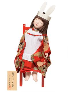 "This doll, called ""Yume Usagi"" (Dream Rabbit) was made by artist Chizuko Inabe. She is clad in a red kimono (appropriately patterned with rabbit and chrysanthemum motifs), apron, and chirimen rabbit headband."