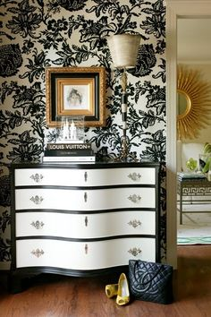 Large black and white print on the wall. Black and white dresser. Looks great. Perfect for a dining room.