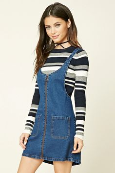 A denim overall dress featuring button front straps, a burnished zip front, and front patch pockets.