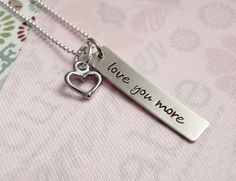 """Sterling Silver Tag Hand Stamped with the saying """"love you more"""". Accented with a Silver Heart Charm."""