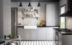 A country kitchen with grey inset doors, black worktops and chrome handles and knobs.
