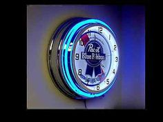 """A high quality double neon clock powered by 12V AC/DC power supply Perfect for the PBR Lover! Approximate size: 19"""" x 19"""" x 5.5"""" Chrome housing finish Two neon glass rings BLUE neon ring on outside WH"""