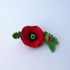Máky  Háčkovaná brož.  Uháčkovaná z bavlny,mírně spevněná drátky a přiškrobená.Zezadu je přišit brožový můstek.Prostředek je vyroben černých drátkú a perliček. Velikost květu je 5-5,5 cm , celá brož 9 cm.