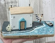 HEADLAND COTTAGE Handcrafted original artwork by DriftwoodSails  A whitewashed coastal cottage with chimneys, set on the edge of the ocean. Outside there is a washing line and a little rowing boat, ready for trips around the headland. This artwork has been lovingly handpainted and