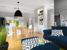 granatowa kanapa z poduszkami w geometryczne wzory; prosty, drewniany, kwadratowy stół.