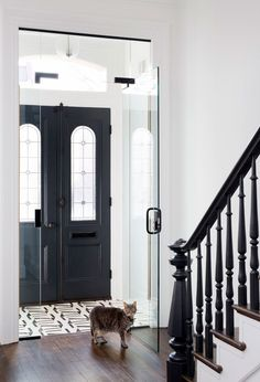 Black front double doors accented with leaded glass panels open to a black and white vestibule fitted with ivory and black geometric floor tiles and a double glass doors.