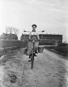 Lady bicycling while carrying two buckets of milk on her shoulders. #netherlands #nederland #holland