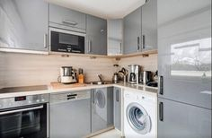 Moderne Küche in Münchner Wohnung mit Fronten in Metall-Optik und heller Arbeitsfläche.  Wohnen in München.  #Munich #kitchen #Küche