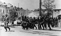 1941, Union Soviétique, un peloton de soldats allemands traversent une rue au pas de course pendant les combats