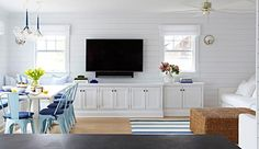 Open plan blue and white beach bungalow living room boasts a shiplap wall holding a flat panel TV mounted between two windows dressed in white roman shades and over white built in cabinets adoring vintage inset hardware lit by Pelham Moon Lights.