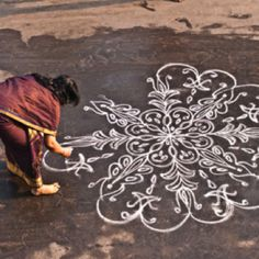 """""""please read: Kolam is a form of sand painting that is drawn using rice powder by female members of the family in front of their home. It is widely practiced by Hindus in South India. A kolam is a sort of painted prayer - a line drawing composed of curved loops, drawn around a grid pattern of dots. Kolams are thought to bestow prosperity to homes."""""""