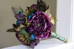 Isn't this a stunning purple and blue bouquet? Fantastic idea to add a few peacock feathers as a highlight.