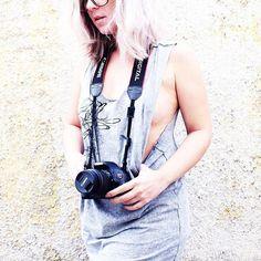 Foto de uma garota loira segurando uma câmera Canon T3i pendurada no pescoço com uma regata cinza mescla cavada