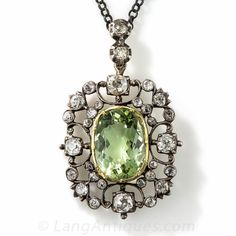 Georgian Antique Green Beryl and Diamond Pendant. A gorgeous 5.15 carat light yellowish green beryl (the same material as emerald, but a lighter hue) is framed by an openwork scroll motif glittering with 1.50 carats of old mine-cut diamonds set in silver. This lovely early nineteenth century Georgian jewel, most likely originating from Great Britain, measures 1 1/2 by 1 inch and suspends from a silver 18 inch chain.