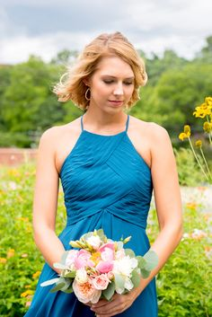 Mikkel Paige Photography photos from a wedding in Durham, North Carolina. Picture of the maid of honor with yellow flowers behind her, in a teal halter top dress, holding a bouquet of peonies and eucalyptus.