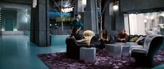In this still image from the movie The Hunger Games, the District 12 tributes, Katniss and Peeta, are gathered in their penthouse with their team, Effie and Cinna. The chair on the far right is a white Elda Chair designed by Joe Colombo in 1963.