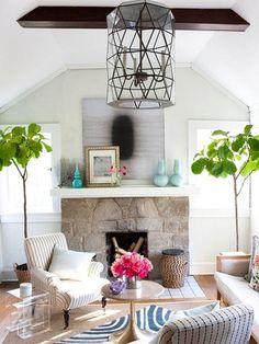 Love the use of color and the fig trees in this room. I don't think the light fixture or the art on the fireplace work with anything else, though.