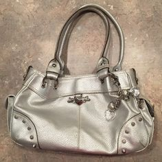 """Kathy Van Zeeland silver bag Silver. 4 pockets - 1 is a zipper and a divider that is a zippered compartment too. Key chain loop sewed into lining. 2 side pockets on the outside. This bag also comes with the famous keychain clip on too.  Measures... 9"""" in height,  13.5"""" width and 4.5"""" depth. The strap has a 9"""" clearing from the top of the bag. Kathy Van Zeeland Bags Satchels"""