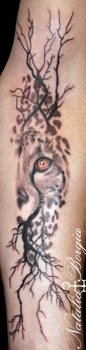 Cheetah with trees abstract tattoo on forearm.