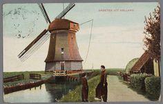 GROETEN UIT HOLLAND. 1900-1910 De watermolen in het Volendammermeertje. Twee jongens in dracht staan bij het water te praten. #NoordHolland #Volendam