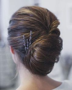 Voluminous French twist with small purple flowers pinned into the hairstyle