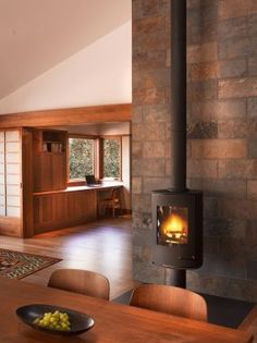 A small, energy-efficient house is made to feel spacious and open by means of an open plan combined with generous areas of glass in the doors and windows, allowing the beauty of the. Dining Room Fireplace, Energy Efficient Homes, Rustic Contemporary, Open Plan, Wood Burning, Fireplaces, Hearth, Interior Inspiration, Stove