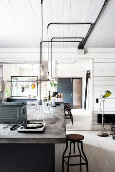 Industrial kitchen with concrete countertops, exposed bulb pendant lights and wooden stools