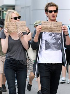 """Cool kids <3  Their signs read: """"We just found out that there are paparazzi outside the restaurant we were eating in. So... why not take this opportunity to bring attention to organizations that need and deserve it?""""  With links to WWO and a cancer support fund"""