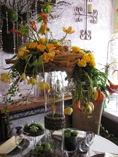 Tall Driftwood Centerpiece on a tall cylinder glass vases with Pale Orange French Tulips, Mango Calla lilies and Yellow Roses