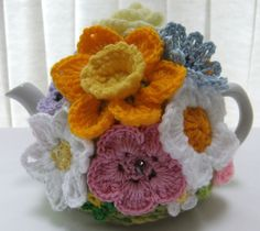 Lovely hand knitted 2 cup spring rose floral tea cosy.  The main body of this tea cosy is knitted in triple double knitting spring toned acrylic wool with several spring toned hand crochet flowers and butterflies crochet in wool/cotton randomly embellished all over the cosy, very pretty, suitable for a two cup tea pot (tea pot not included, for display purposes only)  Please refer to my polices to view my teapot size table to ensure that the correct size of cosy is purchased.