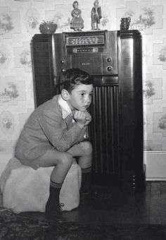 Young boy listening to his family's Philco radio, in the 1940's