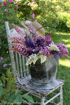 Old Bucket...stuffed with flowers...on an old garden chair.