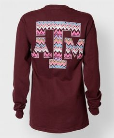 """This maroon longsleeve shirt features our popular multicolored chevron pattern. The front reads """"Texas Aggies"""" and the back has a large block ATM."""