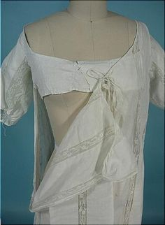 F12-plain front of 1800 gown. Notes with back detail. Under bodice pinned closed and dress pinned at side seam. Draw string at neck, sleeve ends. Vy wide neck, see how little of shoulder seam is left on back detail. Gathering on back fell to rounded train.