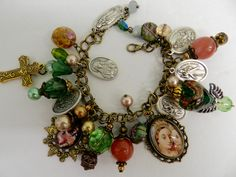 Ornate religious Holy medal Catholic charm bracelet with two framed glass tile pendants that have images ofthe Virgin Mary and Child Jesus.  The double link bronze handmade beaded charm bracelet has green and gold glass pearls and lampworkglass beads with bronze intricate designed findings . There are 1 inch oval shapedHoly medals from Italy and a gold tone cross charm with a green acrylic tulip shaped bead.
