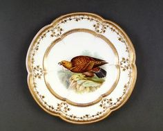 A Coalport six lobed plate painted by John Randall with a golden eagle. The rim is edged and decorated in gilt, the base impressed with two 'Z' s and identified as pattern no. 6/903; circa 1855 - 60.