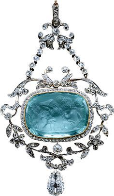 A Belle Epoque pin of an aquamarine cameo with facetted back- 4 Cupids (putti) playing the part of vintagers. Mounted as a pendant within a rose diamond mille-grain border, hanging within an open frame of floral & leafy branches with a pear shaped diamond hanging below, it is attached by chains to the trumpet shaped flower heads & the suspension loop at the top, all diamond set. Cameo: 18th century style. Pendant: 1905.