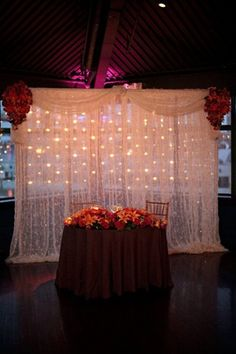 Twinkling Candles Reception Backdrop Draped white fabric with twinkling lights placed behind the sweetheart table at an Indian wedding reception.