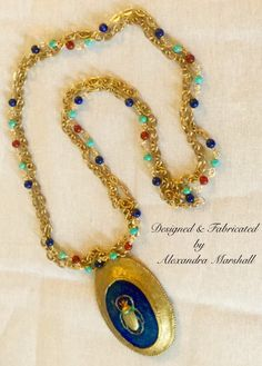 """Love this Egyptian Revival Pendant and (detachable) companion beaded chain necklace by Alexandra Marshall. With exception of the 14K gold overlay (on brass) chain, the bail, and scarab embellishment, this faux finished blue lapis bezeled pendant is made entirely of hand carved clay. Overall length: 40"""". Separate 36"""" companion chain is embellished with lapis color Howlite, turquoise Magnesite, & Carnelian. PN-2-2259. Double click Photo to order."""