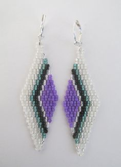 These pretty earrings are handmade with opaque purple, silver-lined teal green, white opal, opaque black, & silver-lined delica seed beads.  They measure 2-5/8 long which includes the plated leverback earwires, & 3/4 wide.