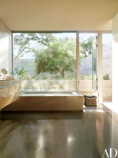 Modern bathroom by Terry Hunziker Inc. and Lake ~ Flato Architects in Austin, Texas Lake Flato, Houses In Austin, Hillside House, Concrete Floors, Plywood Floors, Concrete Lamp, Stained Concrete, Architectural Digest, Amazing Bathrooms