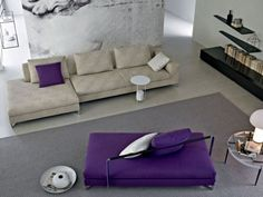 Amazing White Themed Living Room Design with Beautiful Purple Pillow Accessories and Purple Soft Sofa Furniture Design also Elegant Black Wall Shelving Design for Sweet Purple Furniture and Decorations in the Living Room Designs