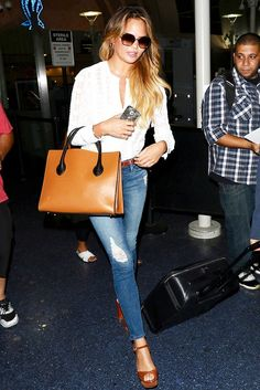 Chrissy Teigen wears a lace blouse, belted skinny jeans, platform heels, retro sunglasses, and a brown leather satchel