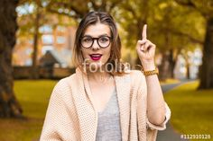 Creative young girl pointing finger up in autumn