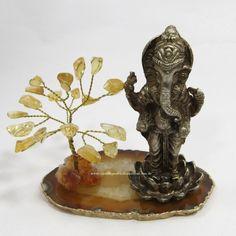 Agata - Ganesha - ID:3755. Ganesha (Deus da fortuna e destruidor de obstáculos) em latão fundido, sobre uma flor de lótus, (pureza do corpo e da mente),    ao lado árvore em Citrino (pedra da prosperidade),  acomodados em chapa de Ágata natural com banho de ouro na borda. A Venda na Loja ou pelo site.