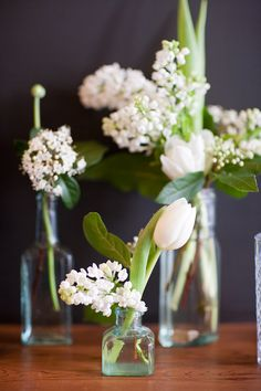 Simple centerpieces of white flowers clustered in vintage bottles