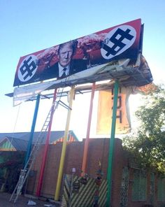 Atompilze mit Clownsgesichtern, davor der Präsident: In den USA zeigt eine Künstlerin ein Donald-Trump-Konterfei neben Symbolen, die an Hakenkreuze erinnern. Nun erhält sie Morddrohungen.