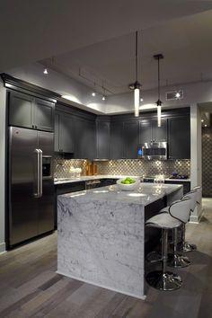 meubles gris dans la cuisine avec un ilot central en marbre blanc