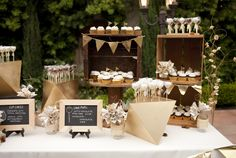 Here's half of our (cup)cake table. We used crates, vintage spools, and handmade chalkboards. My husband made those gold, geometric cake pop holders, and the jars with paper flowers matched my table design and overall aesthetic.